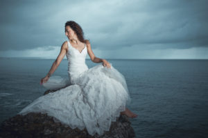 A captivating photograph of a model on the Cornish coastline, taken with a 28mm lens on a rainy summer morning