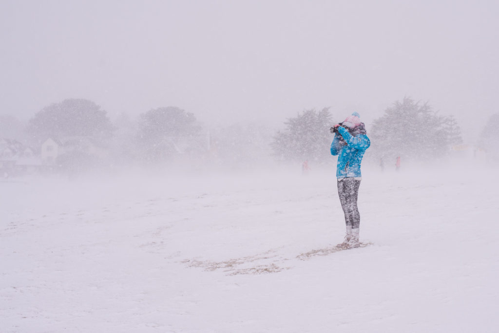 Photographer stands on a snow covered gyllyngvase beach