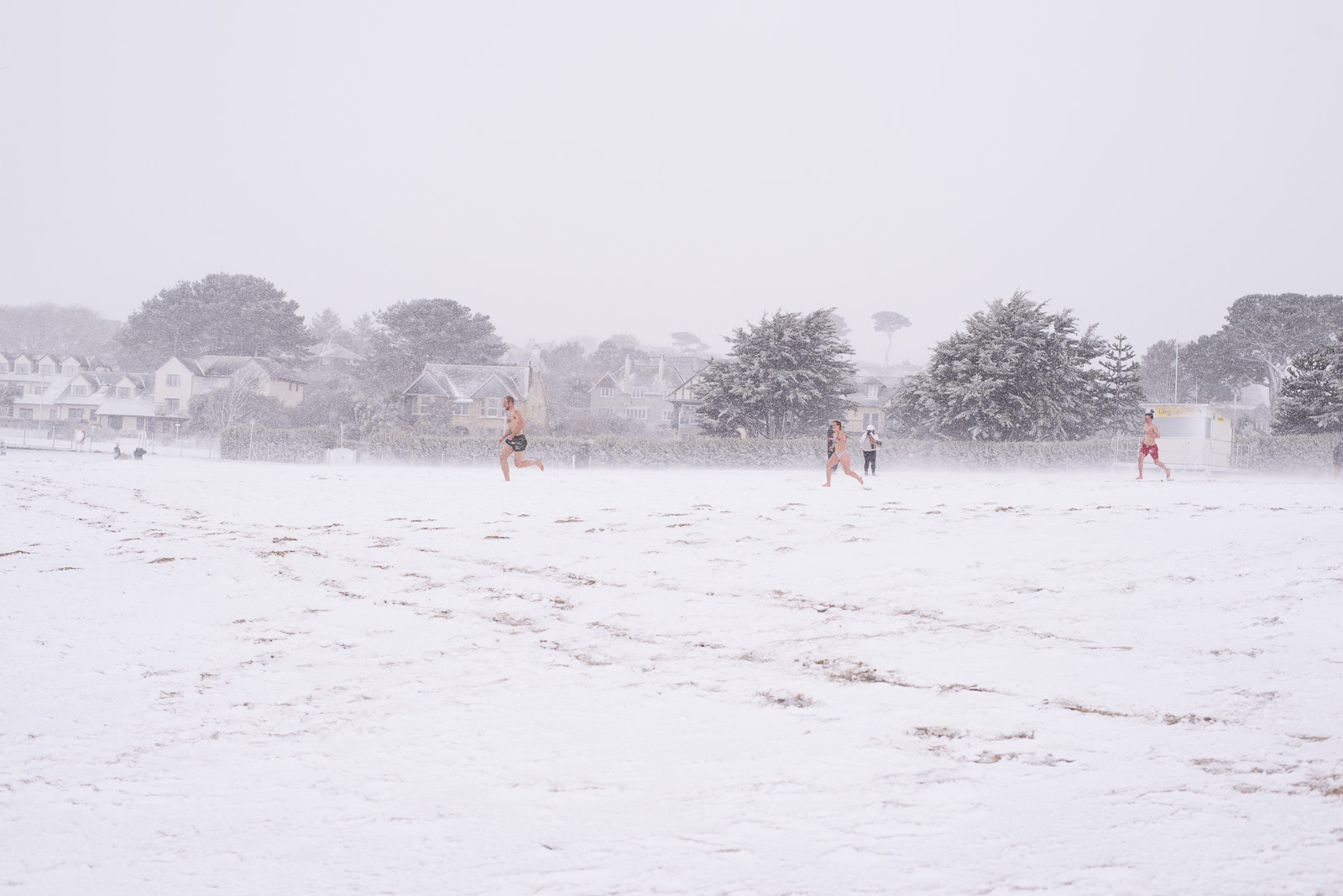 Students run across a snow covered beach at Falmouth