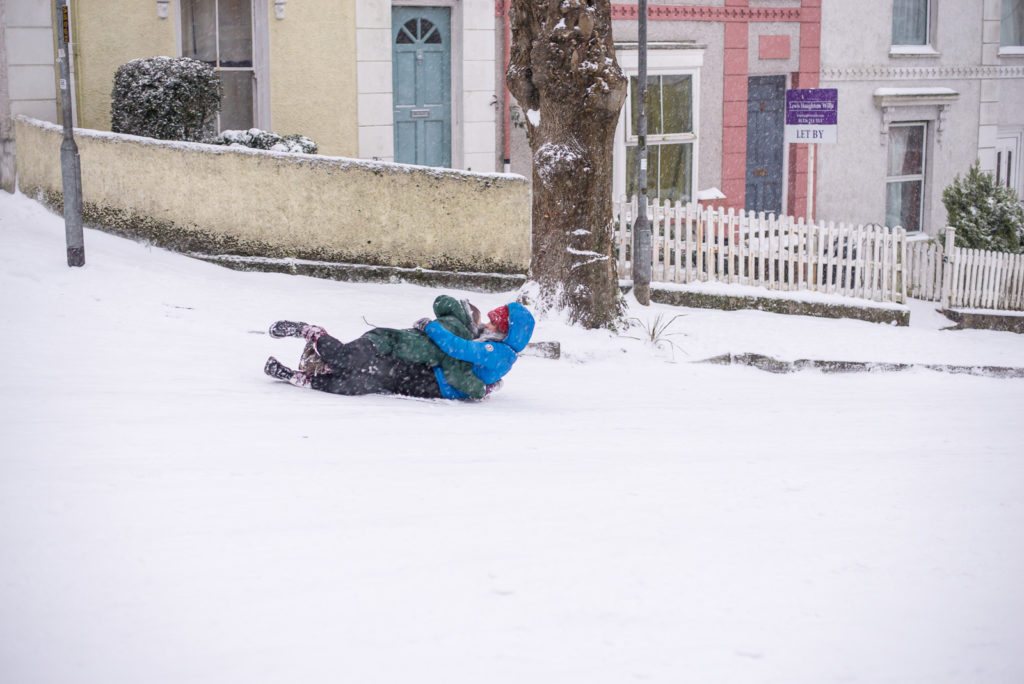 Students use each other as sledges in snow